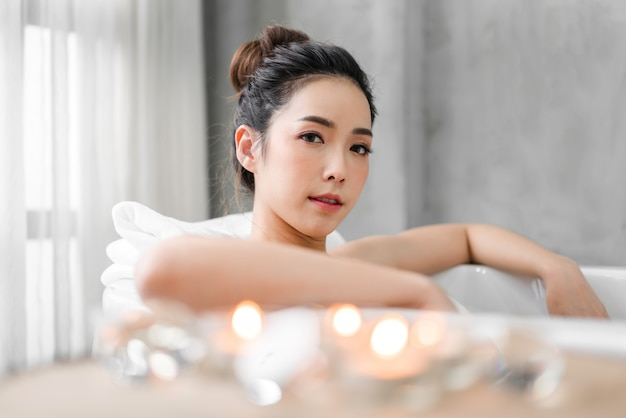 De mooie jonge aziatische vrouw geniet van ontspannend nemend een bad met bellenschuim in badkuip bij de badkamers