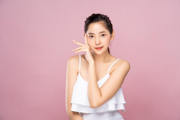 De mooie jonge aziatische vrouw met schone verse witte huid wat betreft haar eigen gezicht zacht in schoonheid stelt.