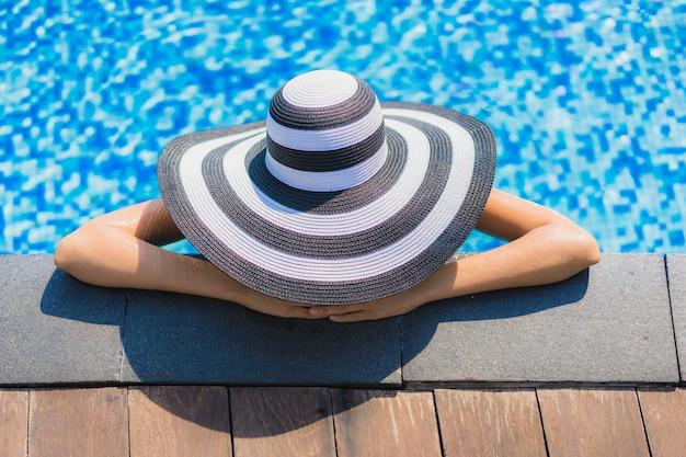 De mooie jonge aziatische vrouwen gelukkige glimlach en ontspant in zwembad