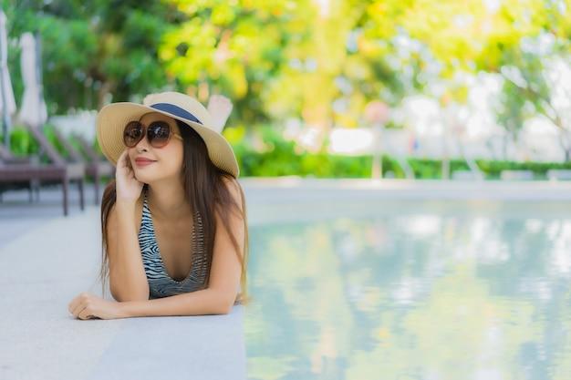 De mooie jonge aziatische vrouwen gelukkige glimlach ontspant rond openluchtzwembad in hoteltoevlucht