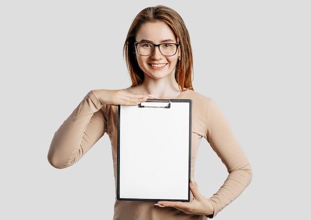 De mooie jonge bedrijfsvrouw die glazen draagt houdt een klembord