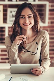 De mooie jonge bedrijfsvrouw gebruikt een digitale tablet.