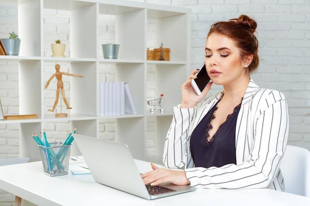 De mooie jonge bedrijfsvrouw gebruikt een smartphone, werkend in bureau