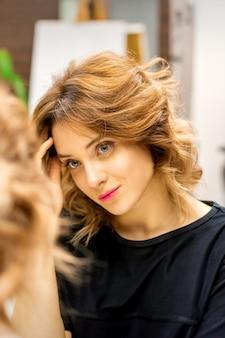 De mooie jonge blanke vrouw kijkt naar haar spiegelbeeld in de spiegel en controleert haar kapsel en make-up in een schoonheidssalon.