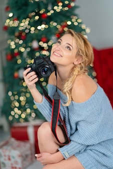 De mooie jonge blonde vrouw met een fotocamera glimlacht naast een kerstboom bokeh.