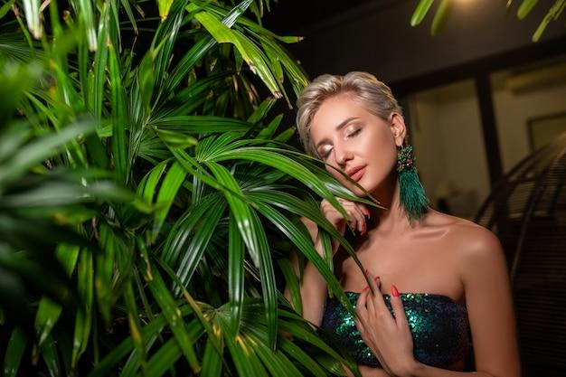 De mooie jonge blondevrouw met perfecte huid en lang lichtblond haar stelt op de aard