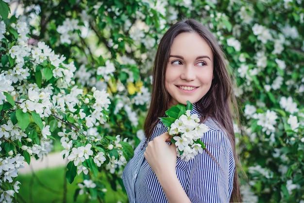 De mooie jonge bomen van de meisjes dichtbij bloeiende appel in de lente