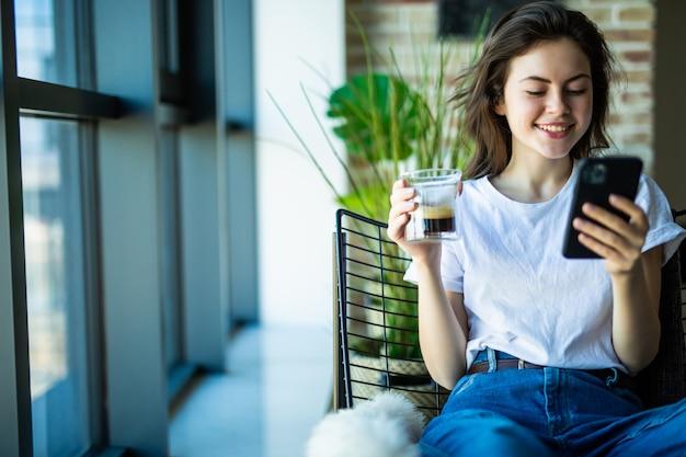De mooie jonge glimlachende vrouw drinkt koffie bekijkend haar slimme telefoon terwijl het zitten als grote comfortabele voorzitter
