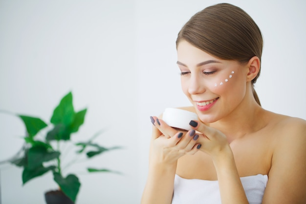 De mooie jonge glimlachende vrouw met schone verse huid kijkt weg, het gezichtszorg van de meisjesschoonheid