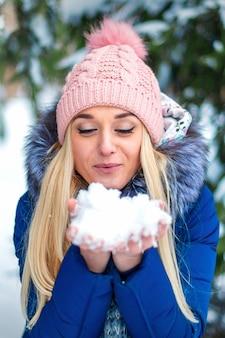 De mooie jonge kaukasische vrouw die op de sneeuw houdt die het in haar houdt dient de winterbos in