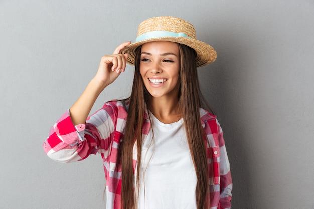 De mooie jonge kaukasische vrouw lacht en wat betreft haar strohoed