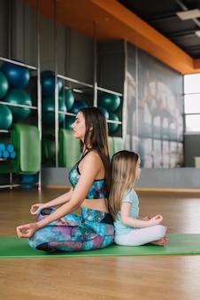 De mooie jonge moeder en haar dochter mediteren terwijl het zitten in yoga stelt