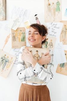 De mooie jonge ontwerper die van vrouwenfahion haar schetsboek houdt
