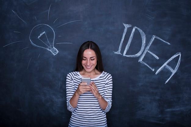 De mooie jonge opgewekte vrouw stelt op een schoolbordachtergrond met een foto van het lampidee.
