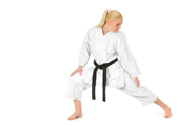 De mooie jonge sportvrouw van de meisjes blonde karate in een kimono maakt een positie om te beginnen met trainen