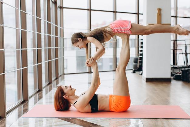 De mooie jonge sterke vrouw en het charmante meisje glimlachen terwijl samen het doen van yoga in geschiktheidszaal