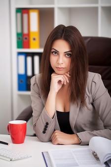 De mooie jonge volwassen schrijver van de bedrijfsfinanciën uitvoerende arbeider op kantoor, met kop koffie