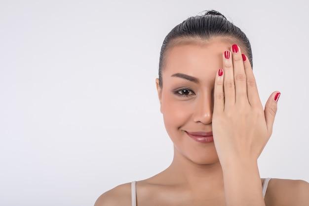 De mooie jonge vrouw behandelt gezicht met handen