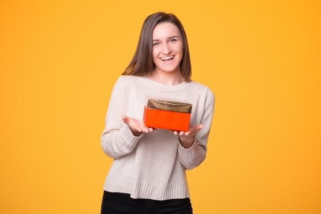 De mooie jonge vrouw biedt je een geschenk aan.