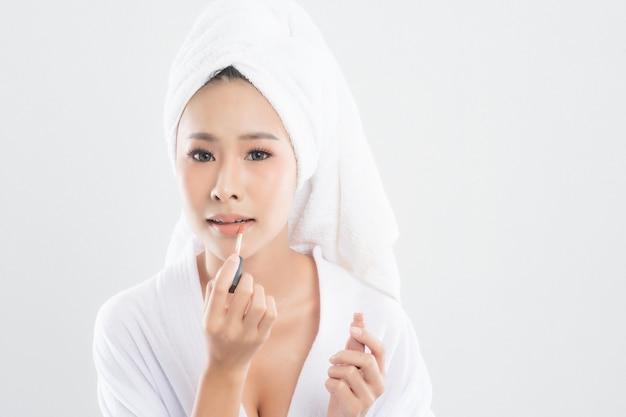 De mooie jonge vrouw die badjas met handdoek met handdoek over hoofd draagt, gebruikt lippenstift om op haar mond te zetten na afwerkingsmake-up die op wit wordt geïsoleerd.