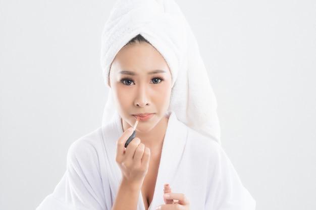 De mooie jonge vrouw die badjas met handdoek met handdoek over hoofd draagt, gebruikt lippenstift om op haar mond te zetten na afwerkingsmake-up