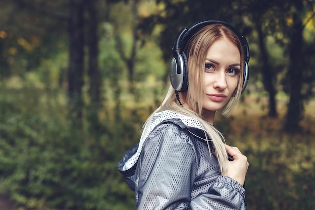 De mooie jonge vrouw die op het stadspark lopen, geniet van luister aan muziek op hoofdtelefoons.