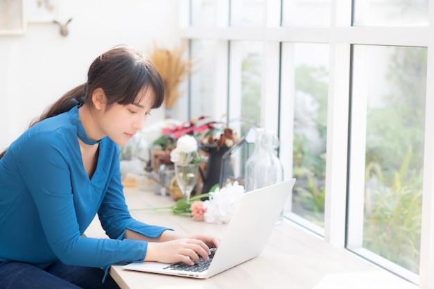 De mooie jonge vrouw die van portretazië online aan laptop werken
