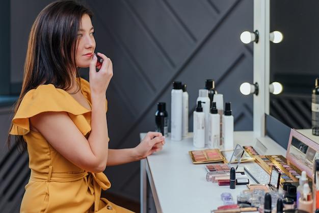 De mooie jonge vrouw doet make-up met behulp van een lipgloss en glimlacht