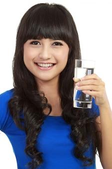 De mooie jonge vrouw drinkt duidelijk mineraalwater van glas.