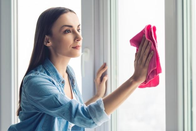 De mooie jonge vrouw gebruikt een vod terwijl het schoonmaken van vensters