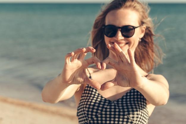 De mooie jonge vrouw geniet de zomer van vakantie op het strand