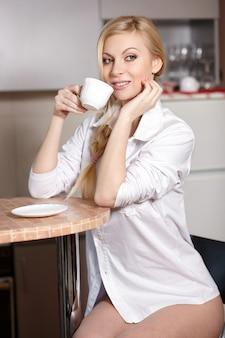 De mooie jonge vrouw houdt een kop van koffie op keuken