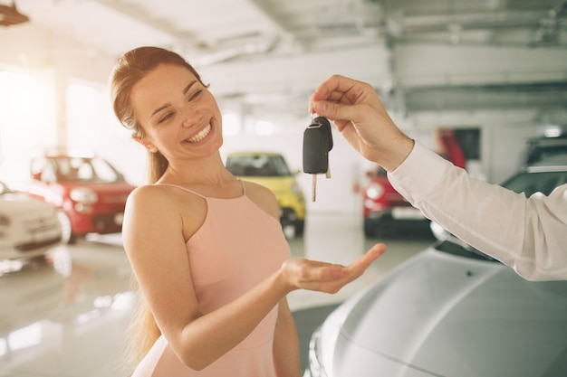 De mooie jonge vrouw houdt een sleutel in autodealer. autozaken, autoverkoop, - gelukkig vrouwelijk model in autoshow of salon.