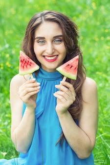 De mooie jonge vrouw houdt twee stukken van watermeloen in haar handen op een groene aardachtergrond