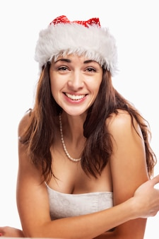 De mooie jonge vrouw in de hoed van de kerstman lacht. verticaal. over wit wordt geïsoleerd.
