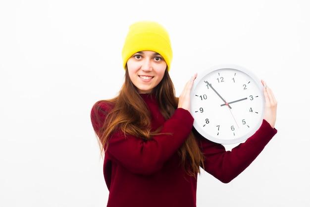 De mooie jonge vrouw in een gele hoed houdt een klok in haar handen glimlachend en kijkend naar het frame