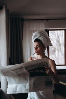 De mooie jonge vrouw in een handdoek rookt een sigaret en leest krant