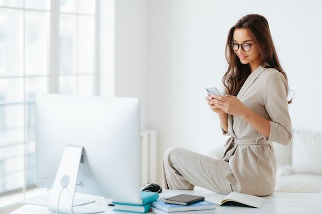 De mooie jonge vrouw in elegante kleren controleert newsfeed via smartphone