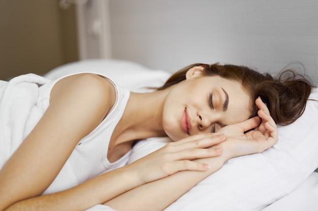 De mooie jonge vrouw in haar mooie sneeuwwitte bed ontspant en ontspant, mooi bewijsmateriaal