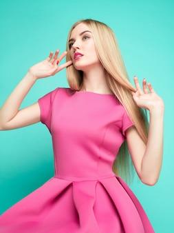 De mooie jonge vrouw in roze mini jurk poseren