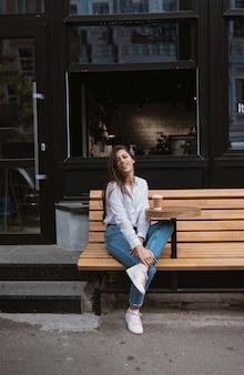 De mooie jonge vrouw in straatkoffie drinkt koffie