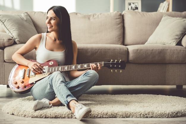 De mooie jonge vrouw in vrijetijdskleding speelt gitaar.