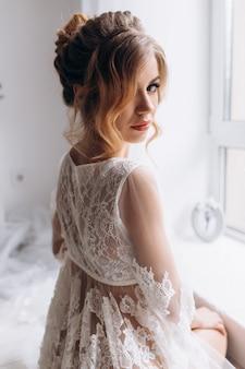 De mooie jonge vrouw in witte lingerie stelt in witte zijdebadjas in heldere hotelruimte