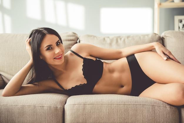 De mooie jonge vrouw in zwarte lingerie bekijkt camera