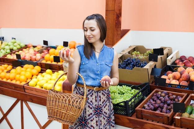 De mooie jonge vrouw kiest perziken in een groentewinkel