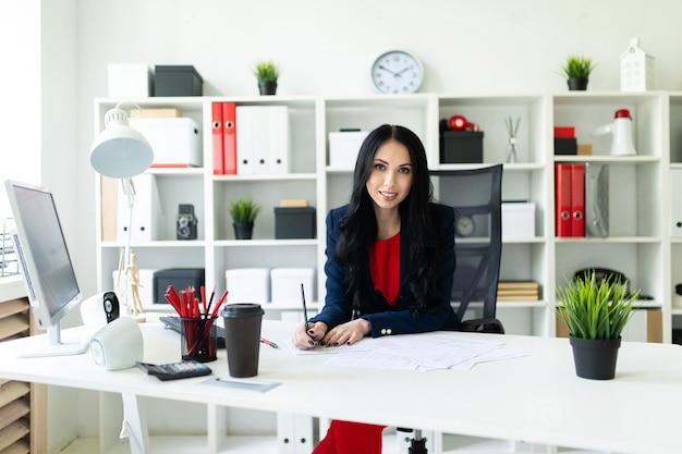 De mooie jonge vrouw kijkt door documenten, zittend in het kantoor aan de tafel.