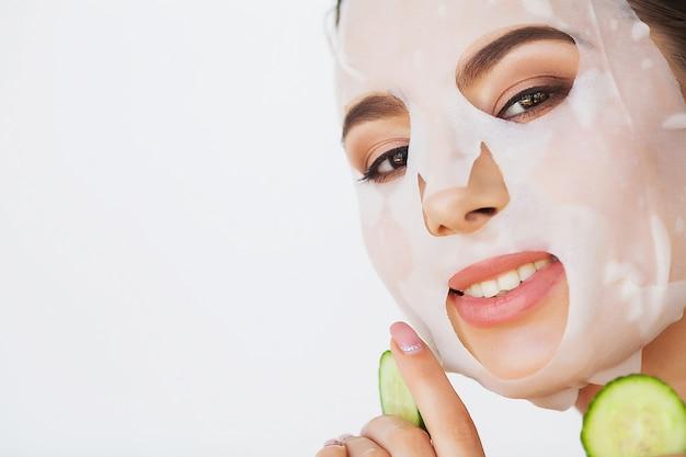 De mooie jonge vrouw krijgt gezichtskleimasker bij kuuroord, liggend met komkommers op ogen