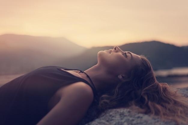 De mooie jonge vrouw ligt op de rotsen door het overzees en lettend op de zonsonderganghemel