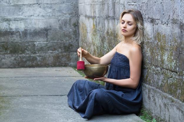 De mooie jonge vrouw met gesloten ogen zit en gebruikt een zingende kom.