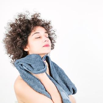 De mooie jonge vrouw met gesloten oog veegt haar gezicht met handdoek af tegen witte achtergrond